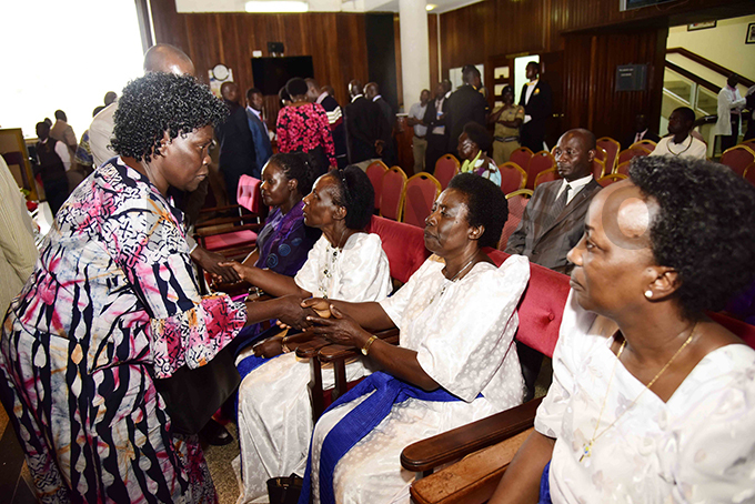 eader of pposition in arliament etty ol chan comforts members of the deceaseds family hoto by ennedy ryema