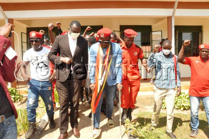 Zaake (with crutches) and supporters leaving court in Mityana on Wednesday. Photos by Luke Kagiri