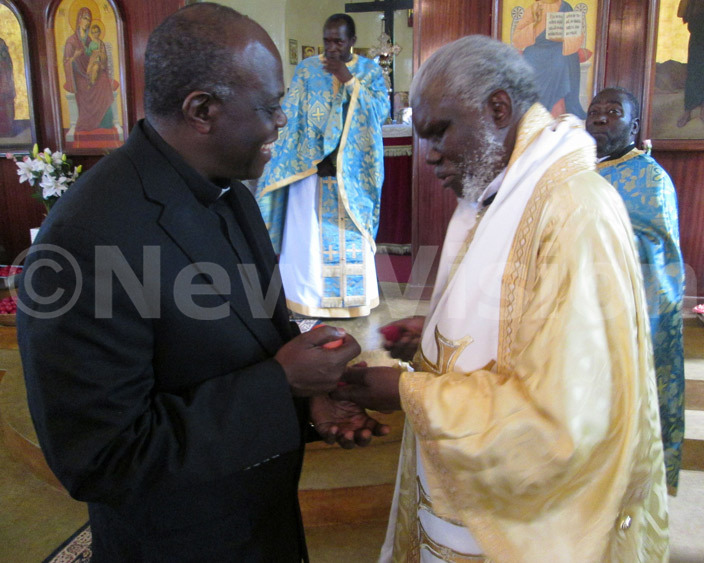 xecutive ecretary r ylvester rinaitwe shares a light moment with rchbishop onah wanga