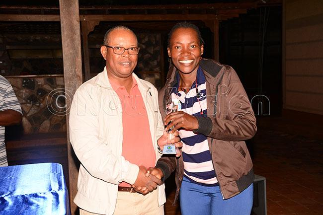 adies roup  winner akalembe right receives his trophy from ohn uchiri