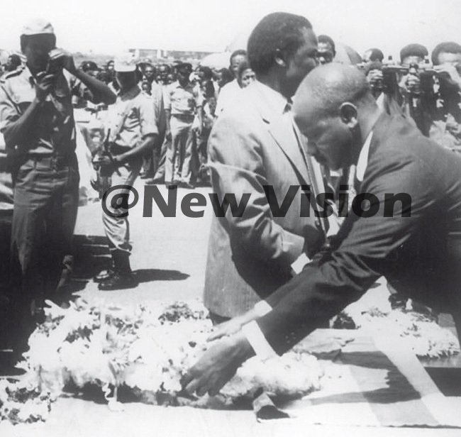 resident useveni lays a wreath on a victims coffin