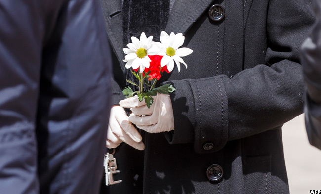man wearing gloves holds flower during the burial of a man who died of the new coronavirus in adrid