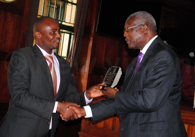 atureebe  is handed the award by  executive director dson girabakunzi hoto by ary ansiime
