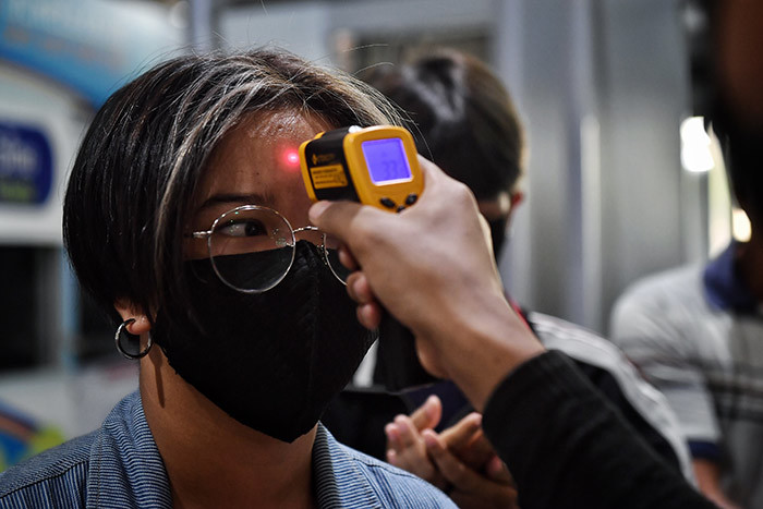 woman has his temperature checked as thousands of migrant workers try to leave the hai capital for their home provinces amid concerns over the spread of the 19 coronavirus at o hit us erminal in angkok on arch 23 2020  ens of thousands of migrant labourers from aos and yanmar flooded bus stations and border crossings in hailand on arch 23 defying requests to stay put to prevent exporting infections of the deadly coronavirus hoto by illian